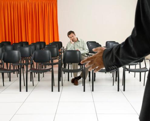 Vortragsraum mit einem Teilnehmer sitzend inmitten leerer Stühle