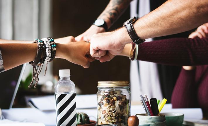 Teamzusammenhalt: 5 Fäuste stoßen zum Einverständnis zusammen. Copyright: rawpixel (pixabay)