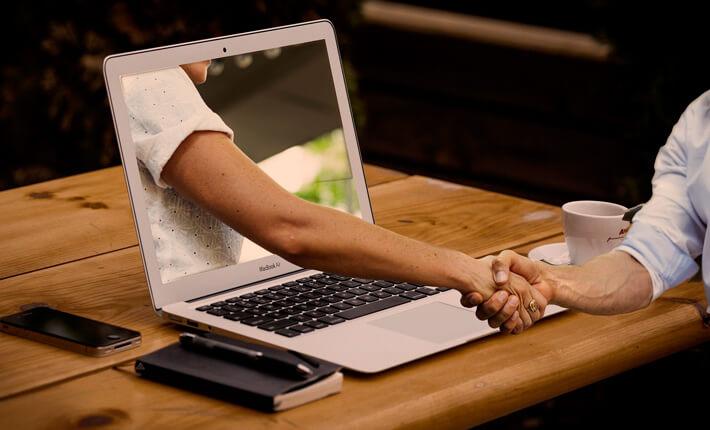 Teams führen Berlin: Hand, die aus einem Laptopmonitor kommend die Hand eines Business Mannes schüttelt.