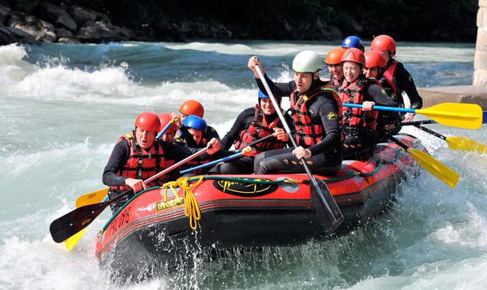 Beidhändige Führung: Gruppe (Team) im Schlauchboot beim Rafting.